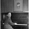 Irving Berlin works at the old piano in his office, with its ...